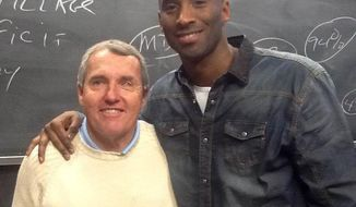 In a photo taken by a student and provided by Boston College, Boston College professor Nick Nugent and Los Angeles Lakers' Kobe Bryant pose for a photo Thursday, Jan. 16, 2014, at Nugent's international marketing class at Boston College in Chestnut Hill, Mass. Boston College says Bryant arrived shortly after the class began and stayed for two hours until it was over. Nugent says Bryant's visit was not planned. (AP Photo/Student photo via Boston College)