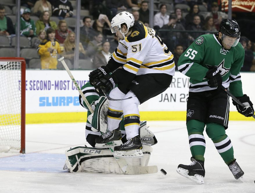 Dallas Stars defenseman Sergei Gonchar (55) helps goalie Kari Lehtonen of Finland, rear, defend the net as Boston Bruins' Ryan Spooner (51) leaps to clear the way for a shot during the second period of an NHL hockey game, Thursday, Jan. 16, 2014, in Dallas. (AP Photo/Tony Gutierrez)