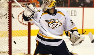 Nashville Predators goalie Carter Hutton looks over his shoulder as the shot by Philadelphia Flyers' Andrej Meszaros goes in the net to tie the game with 3.6 seconds remaining, in the second period of an NHL hockey game, Thursday, Jan. 16,  2014, in Philadelphia. (AP Photo/Tom Mihalek)