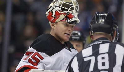 New Jersey Devils goalie Cory Schneider, left, confers with linesman Brian Mach during a timeout against the Colorado Avalanche in the second period of an NHL hockey game in Denver, Thursday, Jan. 16, 2014. (AP Photo/David Zalubowski)