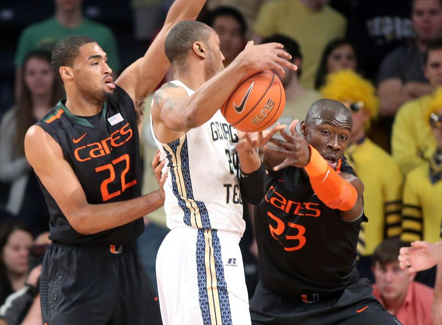 Georgia Tech forward Kammeon Holsey, center, gets defended by Miami forward Donnavan Kirk (22) and center Tonye Jekiri, right, first half of an NCAA college basketball game, Saturday, Jan. 18, 2014, in Atlanta. Miami defeated Georgia Tech 56-42. (AP Photo/Jason Getz)
