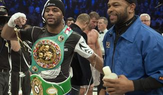 Jean Pascal, left, celebrates with former world champion Roy Jones, as Lucian Bute looks on in the background after winning the WBC Diamond and NABF Light Heavyweight title fight with a unanimous decision Saturday, Jan. 18, 2014 in Montreal. Pascal won the fight with a unanimous decision. (AP Photo/The Canadian Press, Ryan Remiorz)