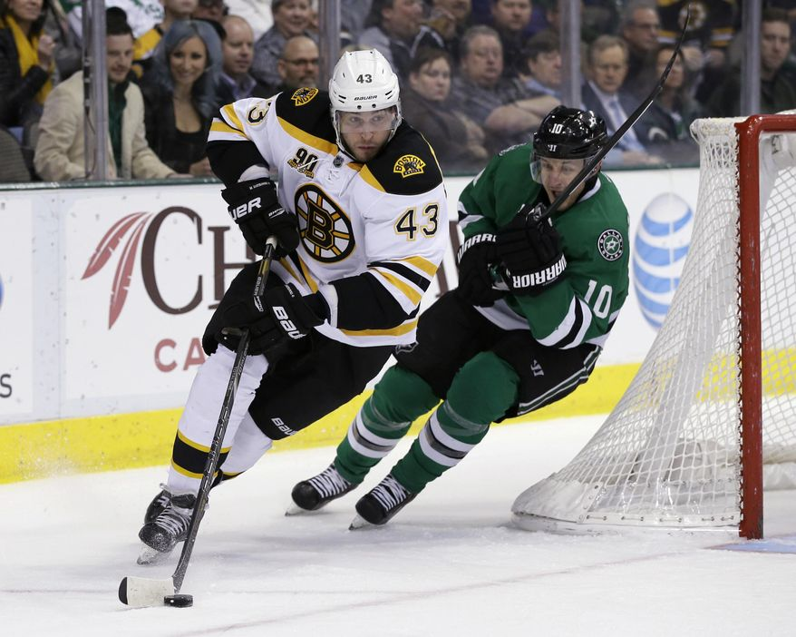 Boston Bruins defenseman Matt Bartkowski (43) helps clear the puck from behind the net as Dallas Stars' Shawn Horcoff (10) gives chase during the first period of an NHL hockey game, Thursday, Jan. 16, 2014, in Dallas. (AP Photo/Tony Gutierrez)