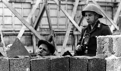 ANOTHER BRICK in the wall: A soldier in East Germany stands guard as the Berlin Wall is built, dividing the city from 1961 to 1989.