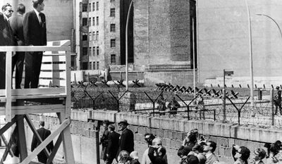 """President Kennedy stands on an observation platform near Checkpoint Charlie to look over the Berlin Wall toward East Berlin. Kennedy delivered his famous speech """"I am a Berliner"""" in front of the city hall in West Berlin during that trip."""