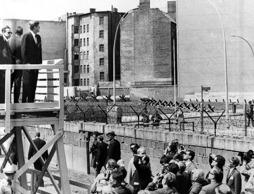"President Kennedy stands on an observation platform near Checkpoint Charlie to look over the Berlin Wall toward East Berlin. Kennedy delivered his famous speech ""I am a Berliner"" in front of the city hall in West Berlin during that trip."