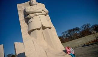 Aliya Logan, 8, and her mother, Lisa, pose for a photograph in front of the Martin Luther King Jr. Memorial on the National Mall on Sunday. (andrew harnik/the Washington Times)