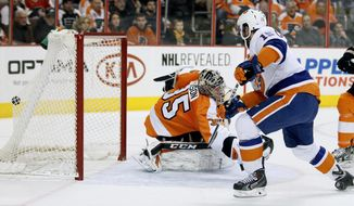 New York Islanders' Cal Clutterbuck, right, puts the puck in the back of the net past Philadelphia Flyers goalie Steve Mason during the first period of an NHL hockey game, Saturday, Jan. 18,  2014, in Philadelphia. (AP Photo/Tom Mihalek)