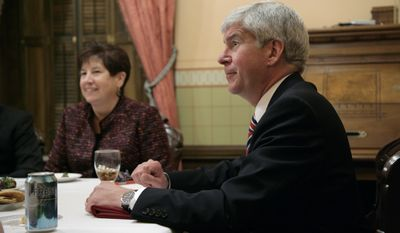 Michigan Gov. Rick Snyder, right, and wife, Sue, enjoy refreshments with family before the State of the State address, Thursday, Jan. 16, 2014, at the state Capitol in Lansing, Mich. (AP Photo/Al Goldis)