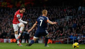 Arsenal's Santi Cazorla, left, scores his side's second goal past Fulham's Steve Sidwell during the English Premier League soccer match between Arsenal and Fulham at the Emirates Stadium in London, Saturday, Jan. 18, 2014.  (AP Photo/Matt Dunham)