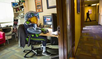 Ryan Asdourian, whose day job is as a Microsoft manager trying to convince developers to create apps for Microsoft platforms, sits in his office Wednesday, Jan. 15, 2014 at the Redmond campus in Redmond, Wash. His other job is being Blitz, the Seahawks' mascot.  (AP Photo/The Seattle Times, Mike Siegel)  SEATTLE OUT; USA TODAY OUT; MAGAZINES OUT; TELEVISION OUT; NO SALES; MANDATORY CREDIT TO: THE SEATTLE TIMESOUTS:  135662