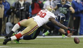 Seattle Seahawks' Russell Wilson and San Francisco 49ers' Aldon Smith go after Wilson's fumble on the first play of the first half of the NFL football NFC Championship game Sunday, Jan. 19, 2014, in Seattle. The 49ers recovered the ball. (AP Photo/Marcio Jose Sanchez)