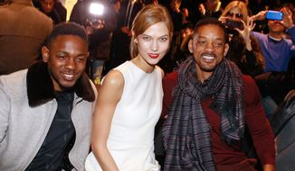 From left, rap singer Kendrick Lamar, model Karlie Kloss and actor Will Smith attend the Dior men's Fall-Winter 2014-2015 fashion collection, presented Saturday, Jan. 18, 2014 in Paris. (AP Photo/Jacques Brinon)