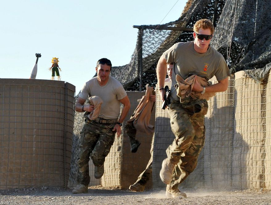 ** FILE ** In this Nov. 3, 2012, file photo, Britain's Prince Harry, right, or just plain Captain Wales as he is known in the British Army, races out from the VHR (very high readiness) tent to scramble his Apache with fellow pilots, during his 12-hour shift at the British-controlled flight-line in Camp Bastion southern Afghanistan. (AP Photo/ John Stillwell, Pool, File)