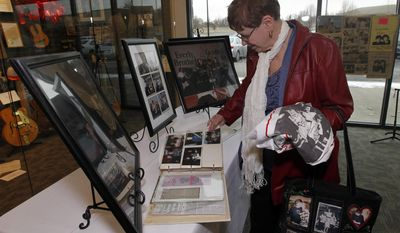 Diana Sue Taylor of Central City, Ky,  a cousin to Phil and Don Everly of the The Everly Brothers look over old photo's and memorabilia of her cousins before a memorial service for Phil Everly at the Merle Travis Music Center in Powderly, Ky, Saturday, Jan. 18, 2014.  (AP Photo/John Sommers II)