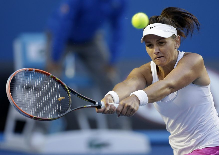 Casey Dellacqua of Australia makes a backhand return to Eugenie Bouchard of Canada during their fourth round match at the Australian Open tennis championship in Melbourne, Australia, Sunday, Jan. 19, 2014.(AP Photo/Rick Rycroft)