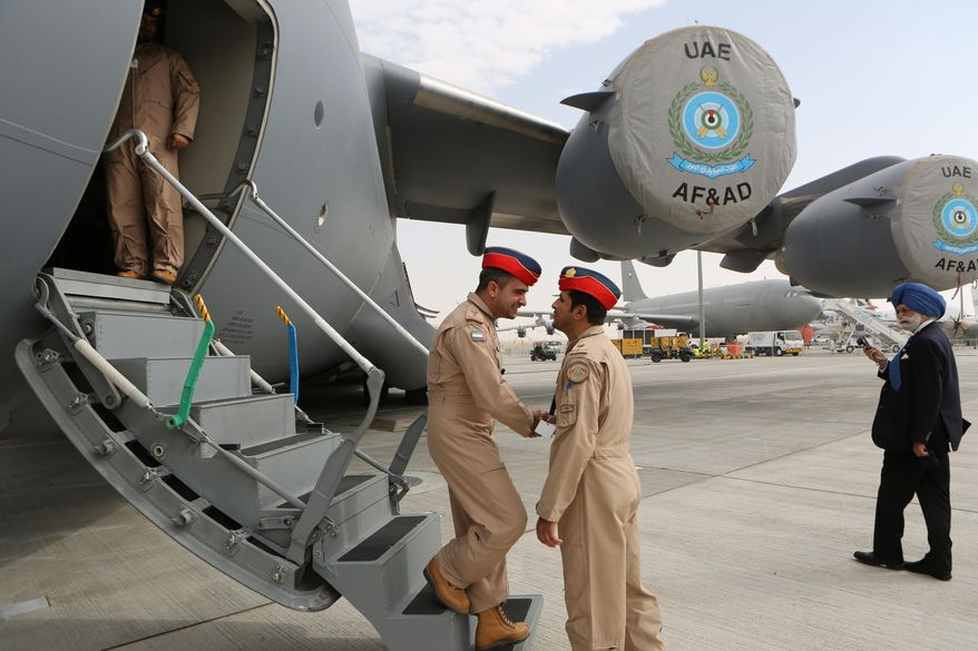 FILE - In this file photo taken Sunday, Nov. 17, 2013, pilots of the United Arab Emirates greet each other at the steps of a Boeing C-17 Globemaster III, a large military transport aircraft of the UAE Air forces, during the opening day of the Dubai Airshow in Dubai, United Arab Emirates. The UAE Prime Minister Sheik Mohammed bin Rashid Al Maktoum said Sunday, Jan. 19, 2014, the Gulf nation has begun the process of imposing mandatory military service for adult males. (AP Photo/Kamran Jebreili, File)