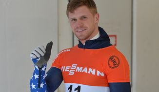 John Daly of the United States gives his thumb up after taking the fifth place at the men's Skeleton World Cup race in Innsbruck, Austria, Saturday, Jan. 18. 2014. (AP Photo/Kerstin Joensson)