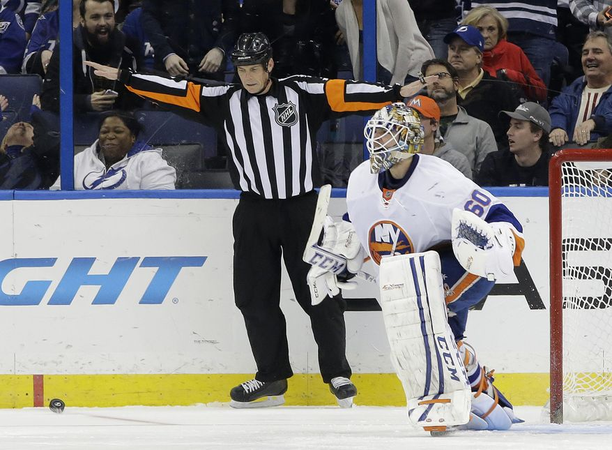 New York Islanders goalie Kevin Poulin (60) celebrates as referee Mike Leggo (3) signals no goal on a shot by Tampa Bay Lightning defenseman Victor Hedman, of Sweden, during a shoot out in an NHL hockey game, Thursday, Jan. 16, 2014, in Tampa, Fla. (AP Photo/Chris O'Meara)