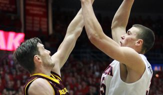 Arizona's Kaleb Tarczewski, right, shoots for two points over the attempted defense of Arizona State's Jordan Bachynski, left, in the first half of an NCAA college basketball game on Thursday, Jan. 16, 2014, in Tucson, Ariz. (AP Photo/John Miller)