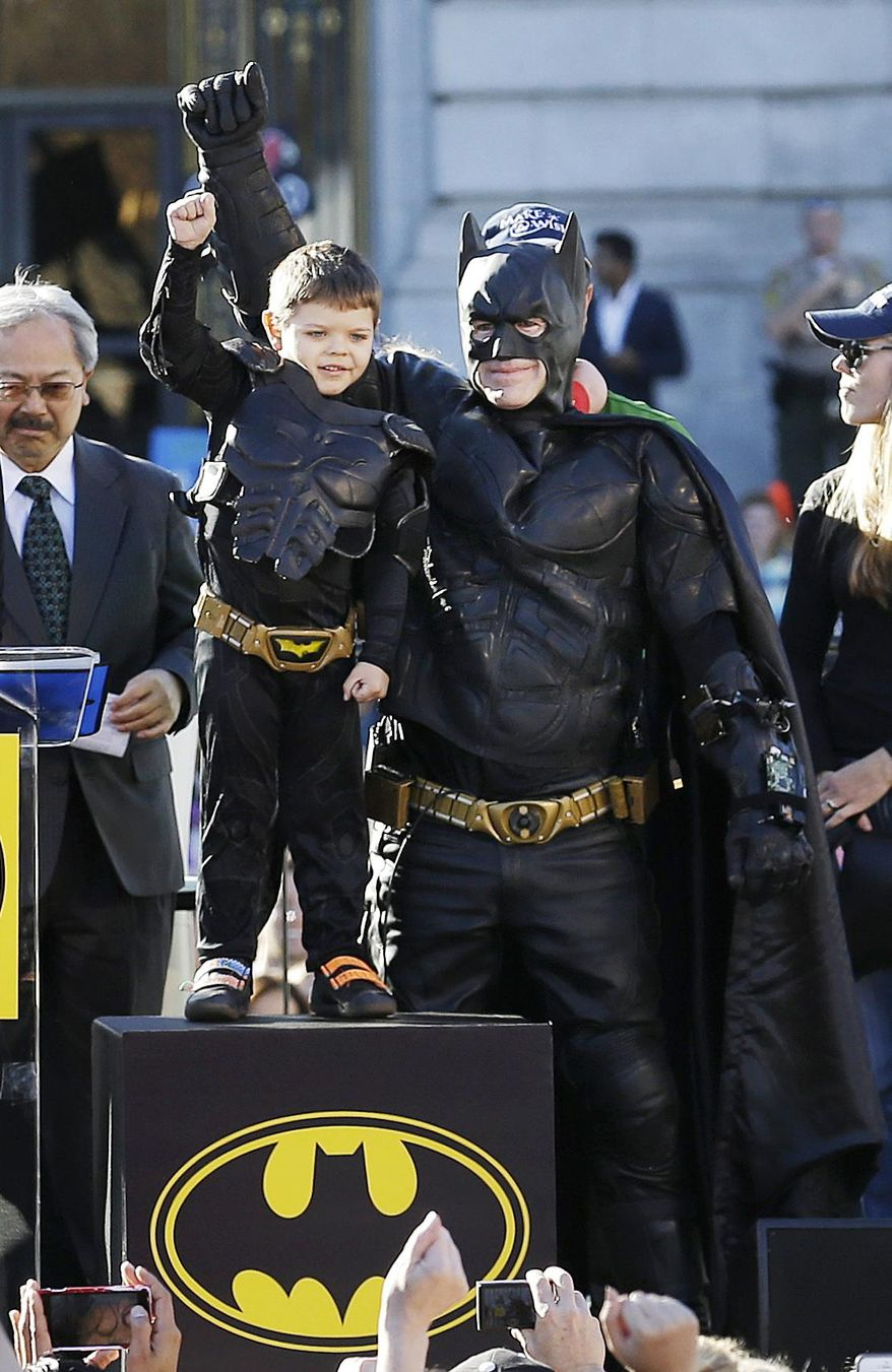 """FILE - This Nov. 15, 2013, file photo, shows Miles Scott, 5, dressed as Batkid, second from left, raising his arm next to Batman at a rally outside of City Hall with Mayor Ed Lee, left, and his mother Natalie Scott, right, in San Francisco. The city of San Francisco is being rescued from paying the cost of staging the """"Batkid"""" fantasy that captured the nation's imagination. Philanthropists John and Marcia Goldman are picking up the city's $105,000 tab for allowing Scott, a Northern California boy with leukemia, to fight villains and rescue a damsel in distress as a caped crusader. (AP Photo/Jeff Chiu, file)"""