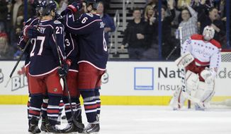 Columbus Blue Jackets players celebrate a goal against Washington Capitals' Braden Holtby, right, during the third period of an NHL hockey game on Friday, Jan. 17, 2014, in Columbus, Ohio. The Blue Jackets won 5-1. (AP Photo/Jay LaPrete)
