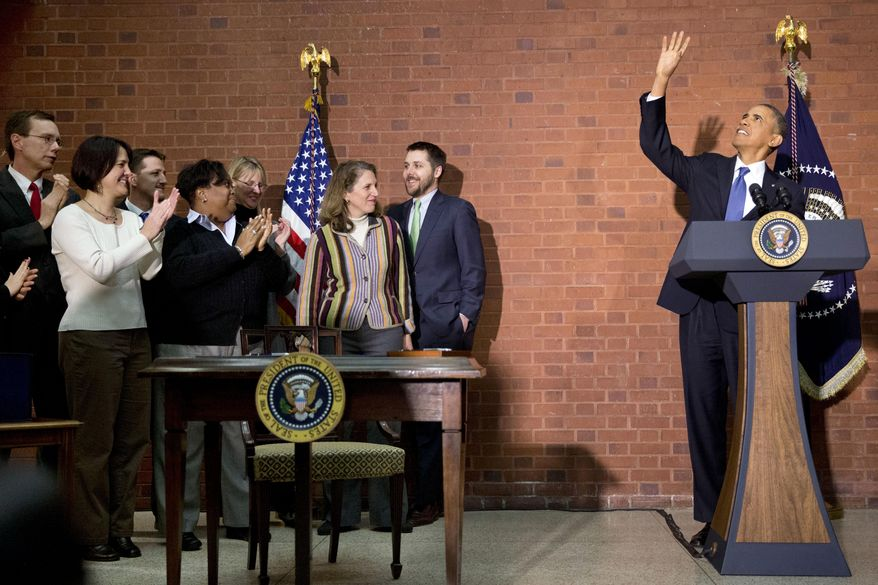 President Barack Obama waves to people in the balcony before signing the $1.1 trillion spending bill that funds the federal government through the end of September, in Washington, Friday, Jan. 17, 2014 at Jackson Place, a conference center near the White House. Obama signed the measure the day before federal funding was set to run out and was joined by aides who did much of the work negotiating it. (AP Photo/Jacquelyn Martin)