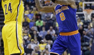 New York Knicks guard J.R. Smith, right, makes a pass over Indiana Pacers forward Paul George during the first half of an NBA basketball game in Indianapolis, Thursday, Jan. 16, 2014.  (AP Photo/Michael Conroy)