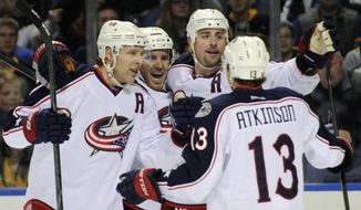 Columbus Blue Jackets' Jack Johnson, left, celebrates with James Wisniewski, center, and Brandon Dubinsky, right, as Cam Atkinson (13) joins in after Dubinsky scored the only goal of the second period of an NHL hockey game against the Buffalo Sabres in Buffalo, N.Y., Saturday, Jan.18, 2014. (AP Photo/Gary Wiepert)