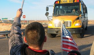 **FILE** Supporters of Berrendo Middle School hold welcome backs signs and balloons while waving American flags and yellow ribbons, greet returning students, parents and teachers back to the school Thursday, Jan. 16, 2014, in Roswell, N.M. Two days after the shooting that involved three students and forced the evacuation and closing of the school. (AP  Photo/Roswell Daily Record, Mark Wilson)