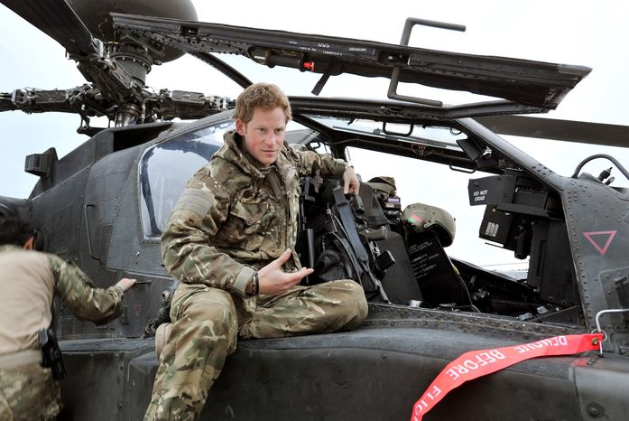 """FILE - In this file photo taken Dec. 12, 2012, made available Monday, Jan. 21, 2013, Britain's Prince Harry or just plain Captain Wales as he is known in the British Army, talks to a TV crew after making his early morning pre-flight checks on the flight-line, from Camp Bastion southern Afghanistan. Palace officials say that Prince Harry is ending his role as a helicopter pilot and taking up a new job with the army in London. Kensington Palace said Harry will now be organizing """"major commemorative events"""" involving the army. (AP Photo/ John Stillwell, Pool, File)"""