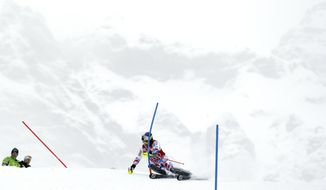 France's Alexis Pinturault clears a gate to clock the fastest time during a slalom portion of a men's alpine ski World Cup super-combined event, in Wengen, Switzerland, Friday, Jan. 17, 2014. (AP Photo/Shin Tanaka)