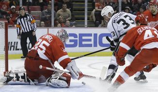 Detroit Red Wings goalie Jimmy Howard (35) deflects a shot by Los Angeles Kings defenseman Willie Mitchell (33) during the first period of an NHL hockey game in Detroit, Saturday, Jan. 18, 2014. (AP Photo/Carlos Osorio)