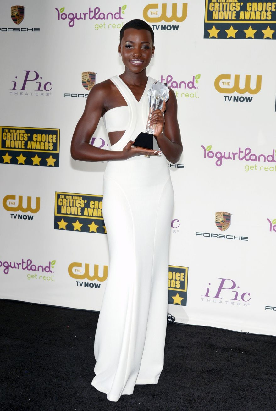 """Lupita Nyong'o poses with the award for best supporting actress for """"12 Years a Slave"""" in the press room at the 19th annual Critics' Choice Movie Awards at the Barker Hangar on Thursday, Jan. 16, 2014, in Santa Monica, Calif. (Photo by John Shearer/Invision/AP)"""