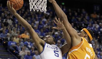 Kentucky's Andrew Harrison, left, shoots under pressure from Tennessee's Jarnell Stokes during the second half of an NCAA college basketball game, Saturday, Jan. 18, 2014, in Lexington, Ky. Kentucky won 74-66. (AP Photo/James Crisp)