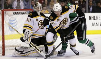 Boston Bruins defenseman Kevan Miller (86) helps goalie Chad Johnson (30) stop a shot under pressure from Dallas Stars' Antoine Roussel (21) during the first period of an NHL hockey game, Thursday, Jan. 16, 2014, in Dallas. (AP Photo/Tony Gutierrez)