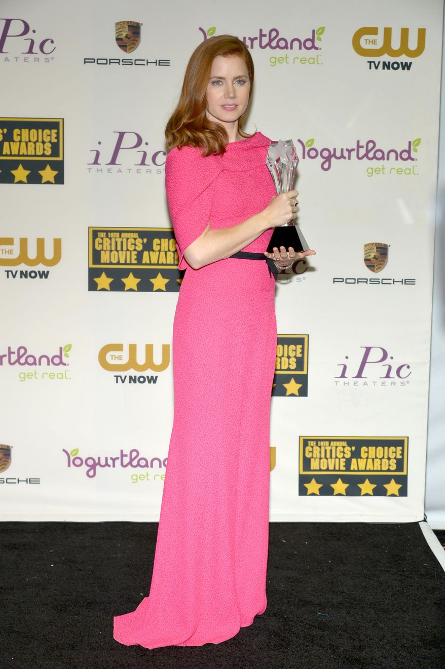 """Amy Adams poses with the award for best actress in a comedy for """"American Hustle"""" in the press room at the 19th annual Critics' Choice Movie Awards at the Barker Hangar on Thursday, Jan. 16, 2014, in Santa Monica, Calif. (Photo by John Shearer/Invision/AP)"""