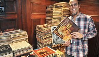 ADVANCE FOR SUNDAY JAN. 19 AND THEREAFTER - In this Monday Jan. 6, 2014 photo, local composer and musician Mark Scarpelli, displays a collection of vinyl records he recently bought, a 1,500-record lot, from another collector on eBay, at his apartment in Charleston, W.Va. He's still going through the records, and occasionally finds some rare ones.  (AP Photo/Charleston Daily Mail, Bob Wojcieszak)