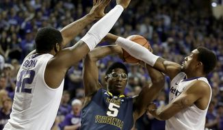 West Virginia's Devin Williams (5) looks to pass the ball under pressure from Kansas State's Thomas Gipson (42) and Shane Southwell during the first half of an NCAA college basketball game Saturday, Jan. 18, 2014, in Manhattan, Kan. (AP Photo/Charlie Riedel)