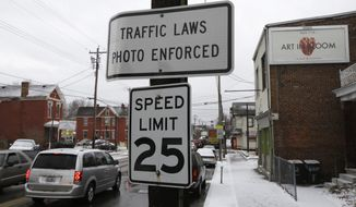 A sign advising motorists they may be monitored by traffic cameras remains in place Thursday, Jan. 16, 2014, in Elmwood Place, Ohio, after the cameras were removed by a ruling from Hamilton County Common Pleas Judge Robert Ruehlman. Judge Ruehlman is set to rule on Jan. 23 whether fines collected by the village must be returned. (AP Photo/Al Behrman)
