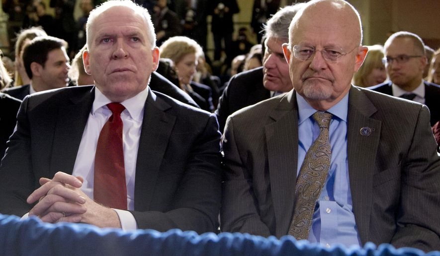 Director of National Intelligence James Clapper, right, and CIA Director John Brennan, left, sit in the front row before President Barack Obama spoke about National Security Agency (NSA) surveillance, Friday, Jan. 17, 2014, at the Justice Department in Washington. The president called for ending the government's control of phone data from millions of Americans. (AP Photo/Carolyn Kaster)