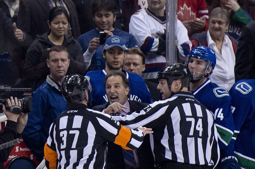 Referees get in the way of Vancouver Canucks head coach John Tortorella as he screams at the Calgary Flames bench during first period NHL hockey action at Rogers Arena in Vancouver,  British Columbia Saturday Jan. 18, 2014. (AP Photo/The Canadian Press, Jonathan Hayward)