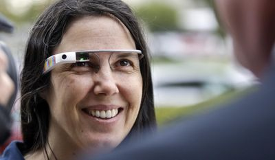 FILE - Cecilia Abadie wears her Google Glass as she talks with her attorney outside of traffic court in this Dec. 3, 2013 file photo taken in San Diego. The California woman believed to be the first cited for wearing Google's computer-in-an-eyeglass while driving says she was within her rights and violated no law. The case to be tried Thursday Jan. 16, 2014 in a San Diego traffic court could help shape future laws on wearable technology as it goes mainstream. (AP Photo/Lenny Ignelzi, File)