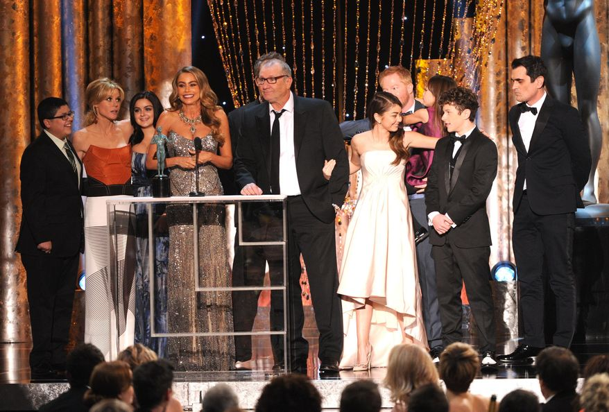 "From left, Rico Rodriguez, Julie Bowen, Ariel Winter, Sofia Vergara, Ed O'Neill, Sarah Hyland, Jesse Tyler Ferguson, Aubrey Anderson-Emmons, Nolan Gould and Ty Burrell accept the award for outstanding performance by an ensemble in a comedy series for ""Modern Family"" at the 20th annual Screen Actors Guild Awards at the Shrine Auditorium on Saturday, Jan. 18, 2014, in Los Angeles. (Photo by Frank Micelotta/Invision/AP)"