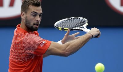 Benoit Paire of France makes a backhand return to Roberto Bautista Agut of Spain during their third round match at the Australian Open tennis championship in Melbourne, Australia, Saturday, Jan. 18, 2014.(AP Photo/Aijaz Rahi)