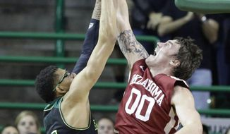 Oklahoma forward Ryan Spangler (00) blocks a shot by Baylor center Isaiah Austin (21) during the first half of an NCAA college basketball game Saturday, Jan. 18, 2014, in Waco, Texas. (AP Photo/LM Otero)