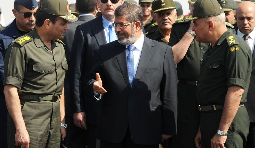 FILE - In this Wednesday, Oct. 10, 2012 file image released by the Egyptian Presidency, Egyptian President Mohammed Morsi, center, speaks with Minister of Defense, Lt. Gen. Abdel-Fattah el-Sissi, left, at a military base in Ismailia, Egypt. Having secured victory in a referendum on a relatively liberal constitution that he championed, insiders say Egypt's military chief is turning his attention to the country's overwhelming array of problems _ from health and education to government subsidies and investment. The revelations offer the latest indication that Gen. Abdel-Fattah el-Sissi is planning a run for president, capping a stunning transformation for the 59-year-old who started in the infantry. (AP Photo/Egyptian Presidency, File) **FILE**