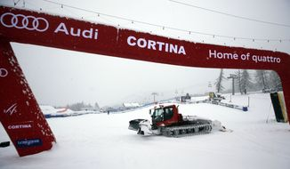 A snow cat moves across the slope after an alpine ski World Cup downhill women's training was canceled due to heavy snowfall continuing from overnight, in Cortina d'Ampezzo, Italy, Friday, Jan. 17, 2013. Forecasts called for up to 30 centimeters (a foot) of fresh snow on the Olympia delle Tofane course. Racers already completed the first training session Thursday, meaning that Saturday's downhill race can still go ahead as scheduled. (AP Photo/Marco Trovati)