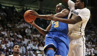 UCLA's Jordan Adams (3) prepares to shoot as Colorado's Wesley Gordon, right, defends during the first half of an NCAA college basketball game in Boulder, Colo., Thursday, Jan. 16, 2014. (AP Photo/Brennan Linsley)