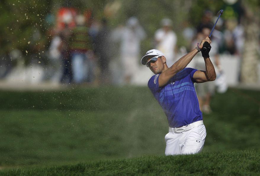 Rafa Cabrera-Bello of Spain plays a bunker shot on the 1st hole during the 2nd round of the Abu Dhabi HSBC Golf Championship in Abu Dhabi, United Arab Emirates, Friday, Jan. 17, 2014. (AP Photo/Kamran Jebreili)